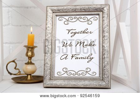 Photo frame on shelf with candlestick on brick wall background