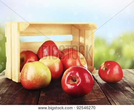 Spilled red apples near crate on wooden table on nature background