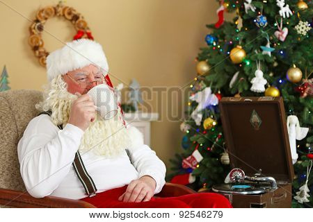 Santa Claus sitting with cup of hot drink in comfortable chair near fireplace at home