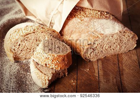 Fresh baked bread wrapped in paper, on wooden background
