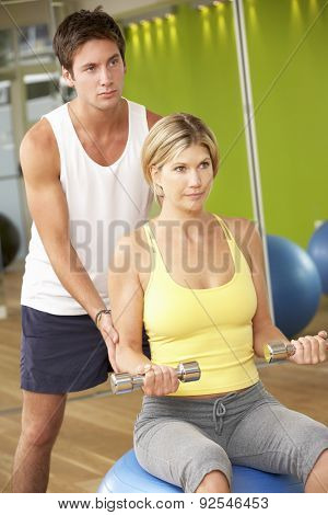 Woman Exercising Being Encouraged By Personal Trainer In Gym