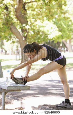 Young Woman Warming Up With Stretches On Park Bench