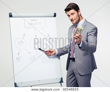 Businessman making presentation on flipchart and holding US dollar bills ovver gray background. Looking at camera