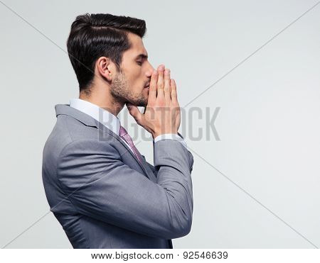 Side view portrait ofa  businessman praying over gray background