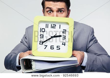 Businessman holding folders and clock over gray background. Looking at camera