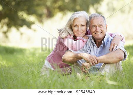 Senior Couple Relaxing In Sunny Summer Field