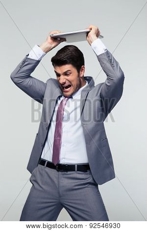 Angry businessman smashing his laptop over gray background