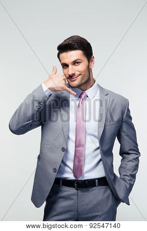 Handsome businessman shwoing call me gesture over gray background. looking at camera