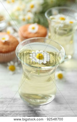 Glass of chamomile tea with chamomile flowers and tasty muffins on color wooden background