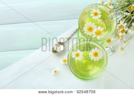 Glasses of chamomile tea with chamomile flowers on color wooden background