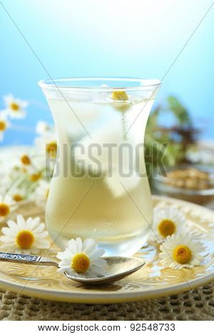 Glass of cold chamomile tea with ice cubes and chamomile flowers on table, on colorful background