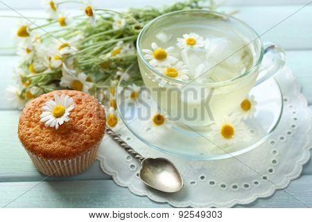 Cup of chamomile tea with chamomile flowers and tasty muffin on color wooden background
