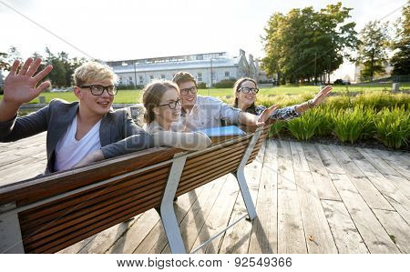 summer holidays, friendship, leisure and teenage concept - group of students or teenagers hanging out and waving hands at campus or park