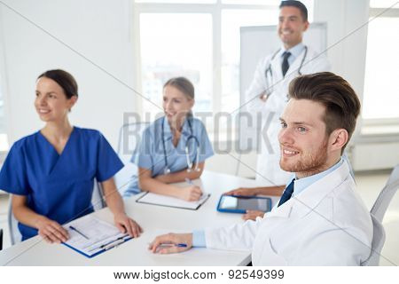medical education, health care, medical education, people and medicine concept - group of happy doctors or interns with mentor meeting on presentation at hospital