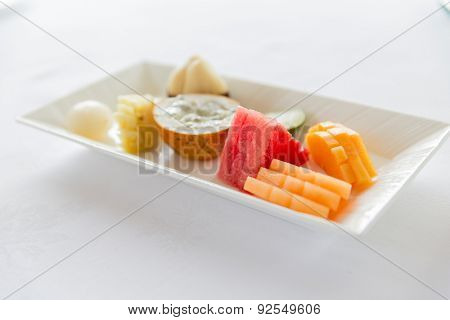 cooking, kitchen and food concept - plate of fresh juicy fruit dessert at restaurant