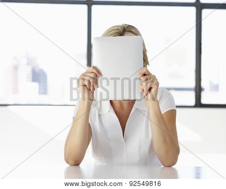 Businesswoman Sitting At Desk In Office With Face Hidden Behind Digital Tablet