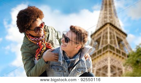 friendship, travel, tourism and people concept - happy international teenage couple in shades having fun over paris eiffel tower background