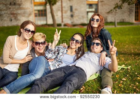 summer holidays, friendship, leisure and teenage concept - group of students or teenagers hanging out and showing victory gesture at campus or park