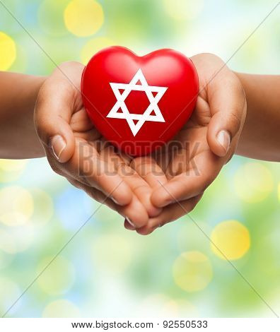 religion, christianity, jewish community and charity concept - close up of female hands holding red heart with star of david symbol over green lights background