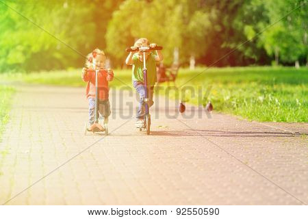 kids riding scooters in summer park
