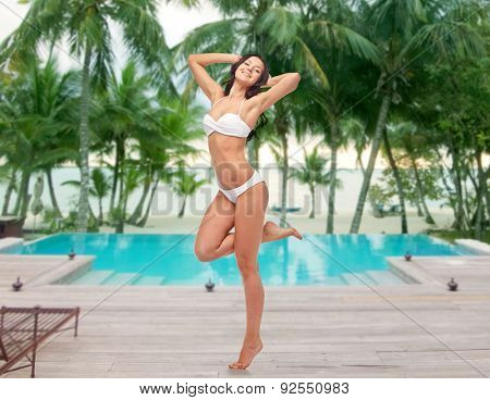 people, fashion, swimwear, summer and beach concept - happy young woman posing in white bikini swimsuit with raised hands and standing on one leg over swimming pool at beach resort