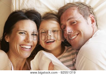 Family Relaxing In Bed