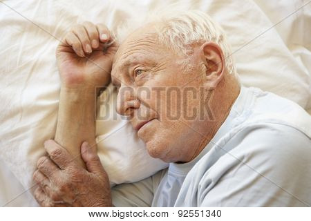 Senior Man Relaxing In Bed