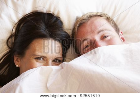 Couple Relaxing In Bed Hiding Under Bedclothes