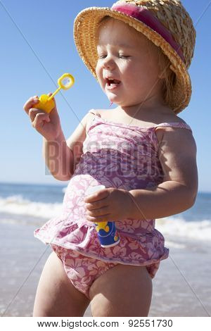 Young Girl Playing With Bubbles On Sunny Beach