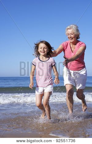 Grandmother Chasing Granddaughter Along Beach