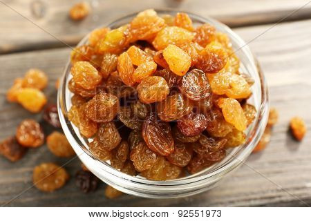 Raisins in glass saucer on wooden table, closeup