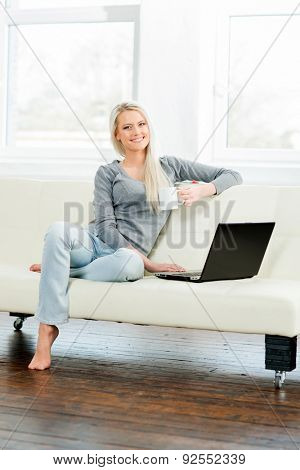 Young and happy woman resting on sofa at home and drinking coffee