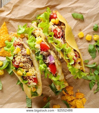 Tasty taco with greens on paper close up