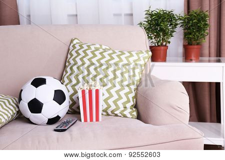 Soccer ball, remote control and box of popcorn on comfortable sofa, indoors