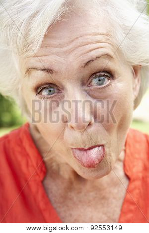 Head And Shoulders Portrait Of Senior Woman Poking Out Tongue