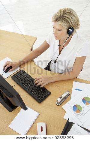 Overhead View Of Service Agent Talking To Customer In Call Centre