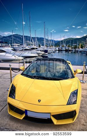 PORTO MONTENEGRO, TIVAT, MONTENEGRO - YULY 18: yellow Lamborghini Gallardo parking in reserved area superyacht marina of Porto Montenegro. Shot in 2014
