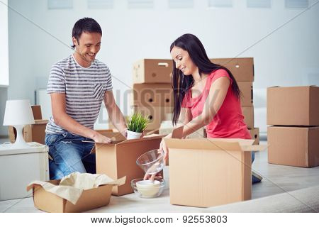 Young couple unpacking boxes after removing to new house