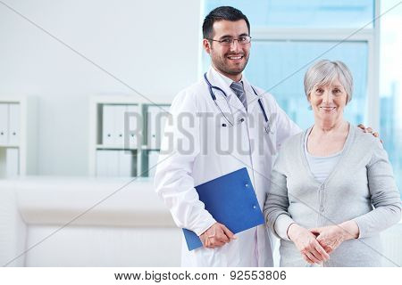 Smiling doctor with clipboard and elderly female patient in clinic