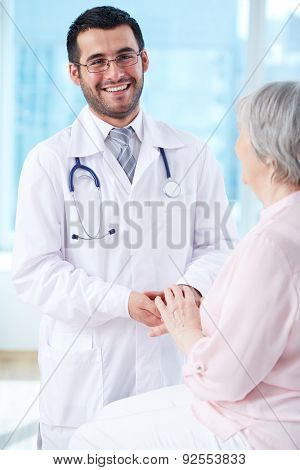 Smiling doctor taking care of his patient in hospital