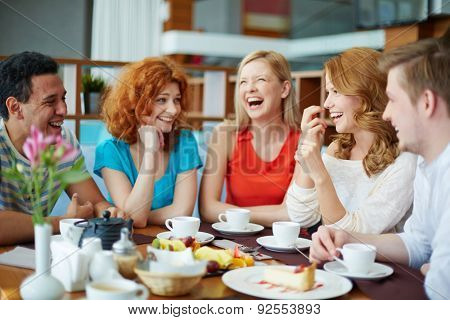 Joyful friends spending time in cafe