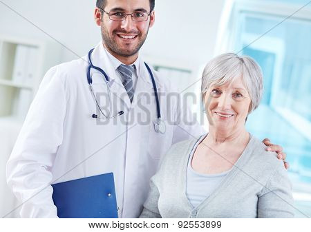 Happy young doctor and elderly female patient