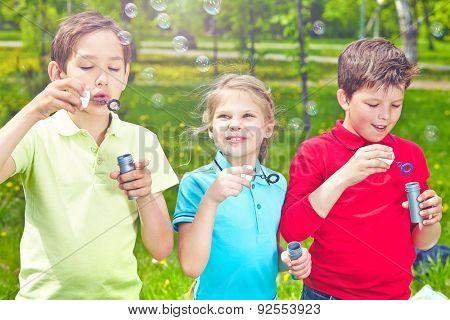 Adorable friends blowing soap bubbles in park