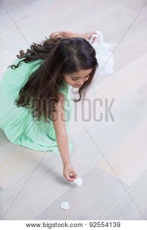 High angle view of girl picking up flower petals from floor at home