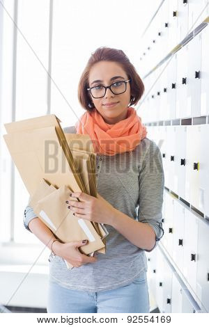 Portrait of confident businesswoman holding envelopes in locker room at creative office