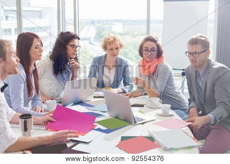 Creative business colleagues analyzing photographs at conference table in office