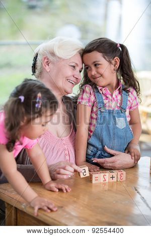 Loving grandmother teaching calculation to granddaughters at table in house