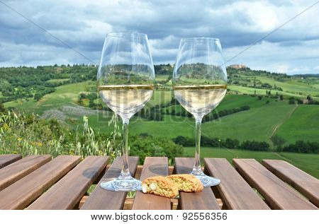 White wine and cantuccini on the wooden table against Tuscan landscape, Italy