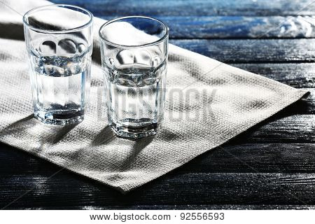 Two glasses of water on table on napkin close up