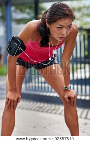 exhausted sporty asian chinese woman runner after fitness running workout outdoors